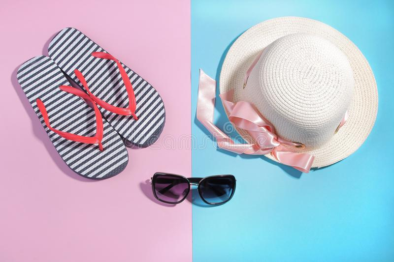 Beach accessories. Flip-flops and a summer hat with sunglasses on a bright pink and blue background. Top view stock photos