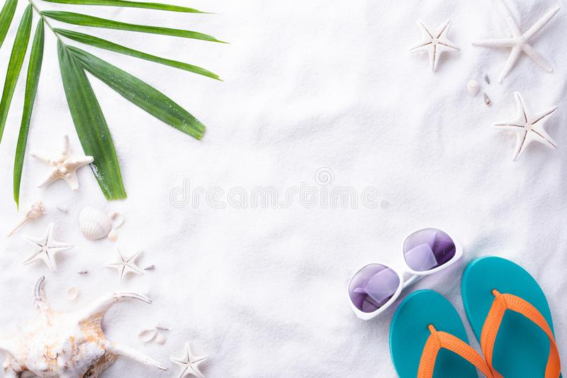 Beach accessories Green tropical leaves with sunglasses, flip flop starfish, beach hat and sea shell on white sand beach. Background for summer holiday and royalty free stock photos