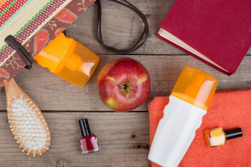 hairbrush, orange towel, sun cream, lotion, beach bag, nail polish, a book on a brown wooden background stock images