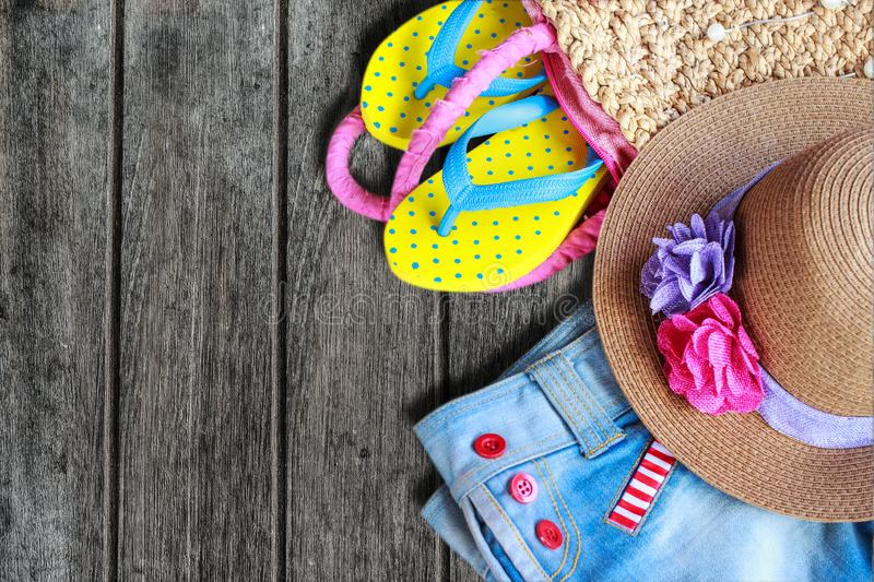 Beach accessories on old wooden background. Yellow sandals, sun hat and Denim shorts stock photography