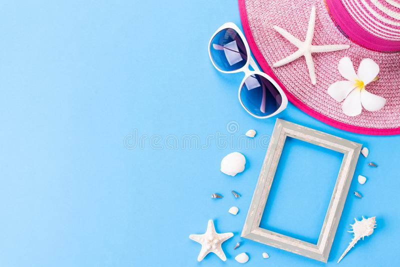 Beach accessories Picture Frame, sunglasses, flip flop, starfish beach hat and sea shell on bright pastel blue sky background for stock photos