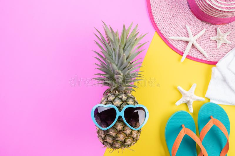 Beach accessories pineapple, sunglasses, flip flop, starfish beach hat and sea shell on pink and yellow background for summer stock photos