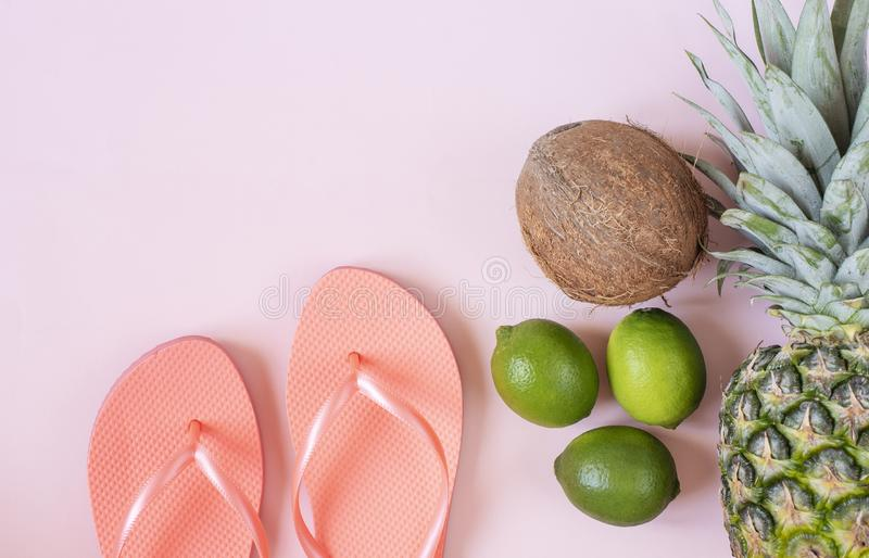 Beach accessories on pink background - pineapple, coconut, lime, flip-flops. Summer is coming concept.  royalty free stock photography