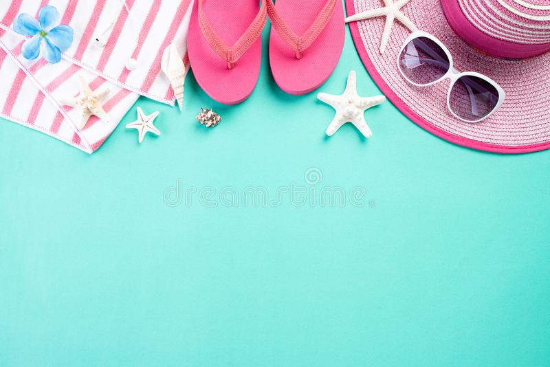 Beach accessories retro film camera, sunglasses, flip flop starfish beach hat and sea shell on green pastel background for summer. Holiday and vacation concept stock image