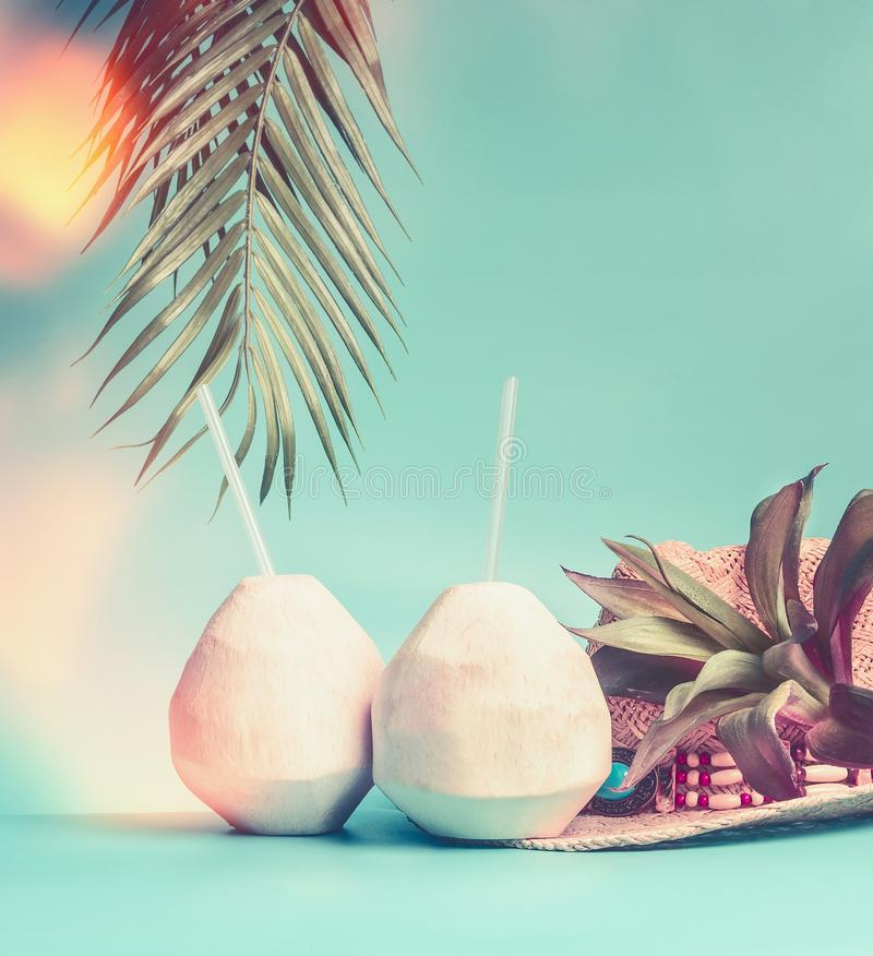 Beach accessories : straw hat, palm leaves and coconut cocktail on blue turquoise background, front view. Summer holiday and tropical vacation travel concept stock photos