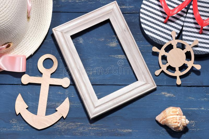 Beach accessories. A summer hat with flip flops, a wooden frame, a wooden anchor and a steering wheel on a blue background. Top vi royalty free stock images