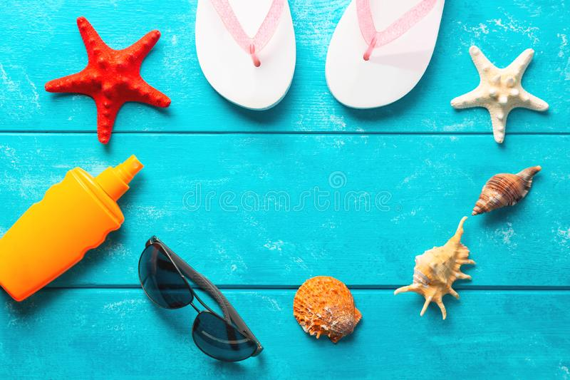Beach accessories. Summer holidays and vacation travel concept. Sunscreen lotion bottle, flip flops, shell ,sunglasses and red. Starfish on pastel blue royalty free stock image