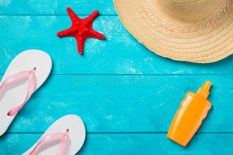 Beach accessories. Summer holidays and vacation travel concept. Sunscreen lotion bottle, straw hat, flip flops and red starfish on. Pastel blue background. Top stock image
