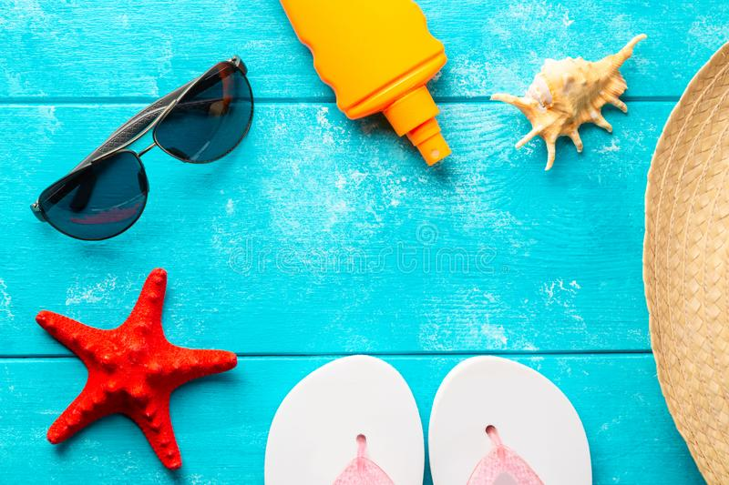 Beach accessories. Summer holidays and vacation travel concept. Sunscreen lotion bottle, straw hat, flip flops, shell, sunglasses stock photography