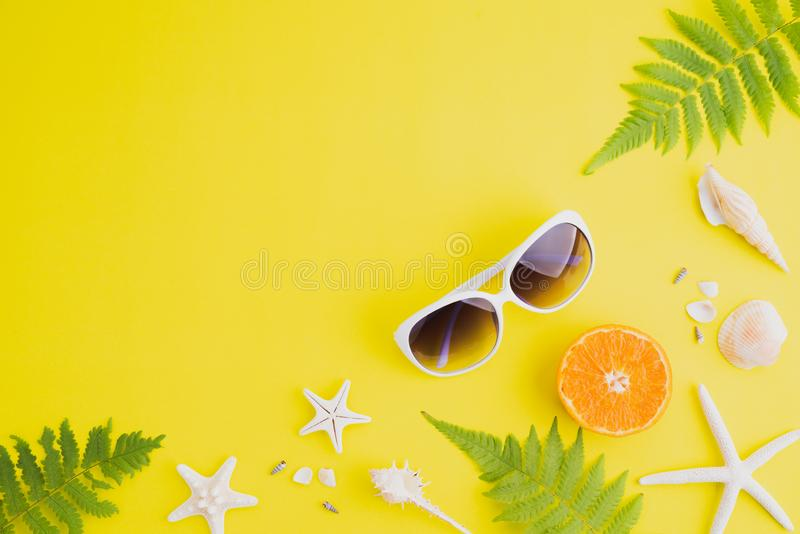 Beach accessories sunglasses, starfish, orange, fern leaves and sea shell on yellow background for summer holiday and vacation. Concept stock photo