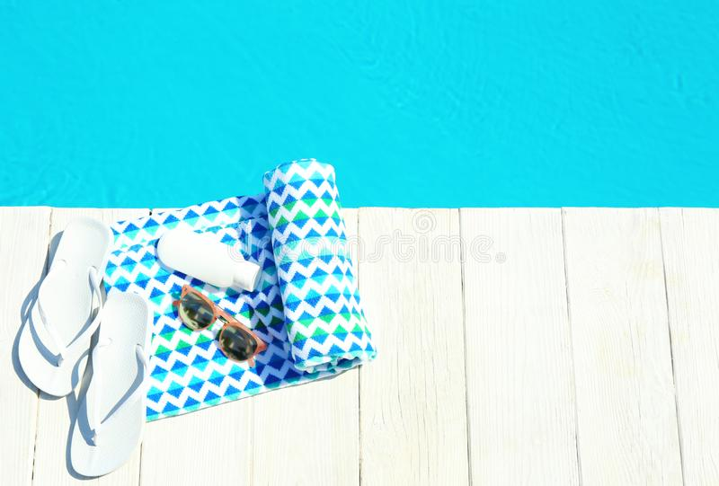 Beach accessories on wooden deck near swimming pool. Space for text. Beach accessories on wooden deck near swimming pool, top view. Space for text royalty free stock photography