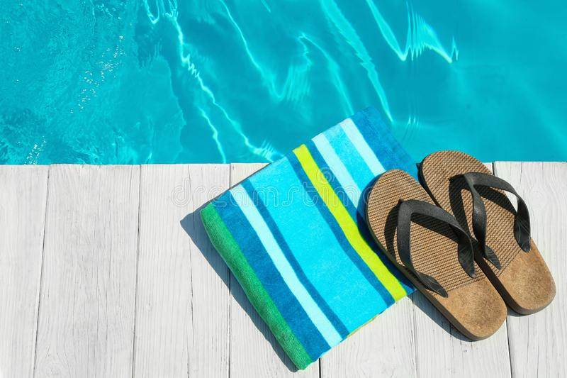Beach accessories on wooden deck near swimming pool. Space for text. Beach accessories on wooden deck near swimming pool, top view. Space for text royalty free stock photo