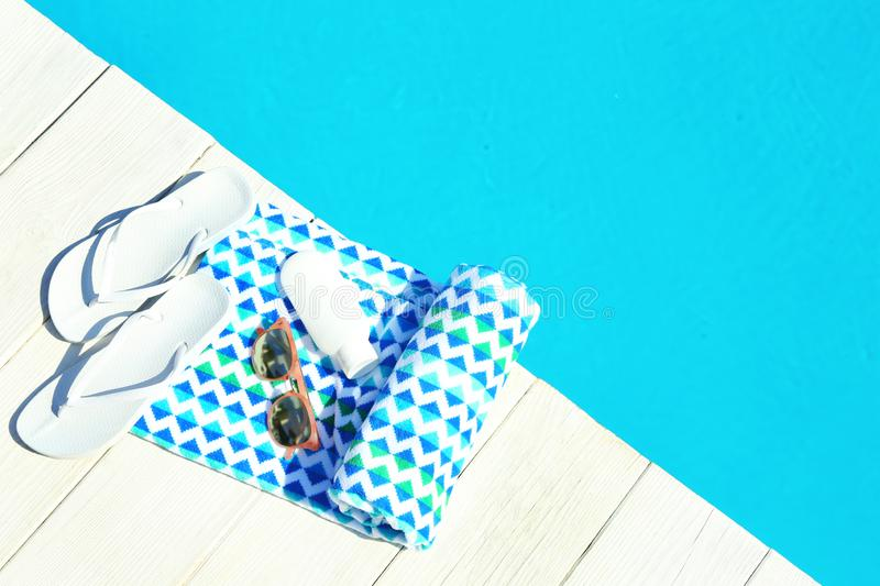 Beach accessories on wooden deck near swimming pool, top view. Space for text royalty free stock images