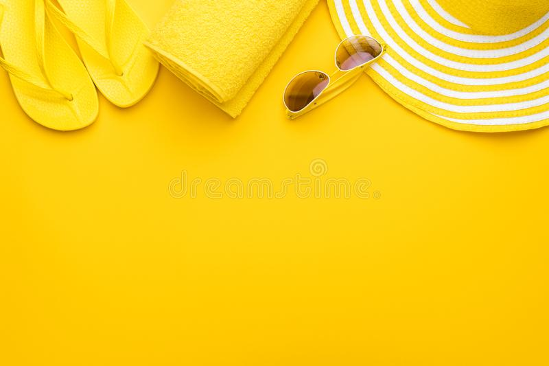 Beach accessories on the yellow background - sunglasses, towel. flip-flops and striped hat. summer is coming concept.  stock photos