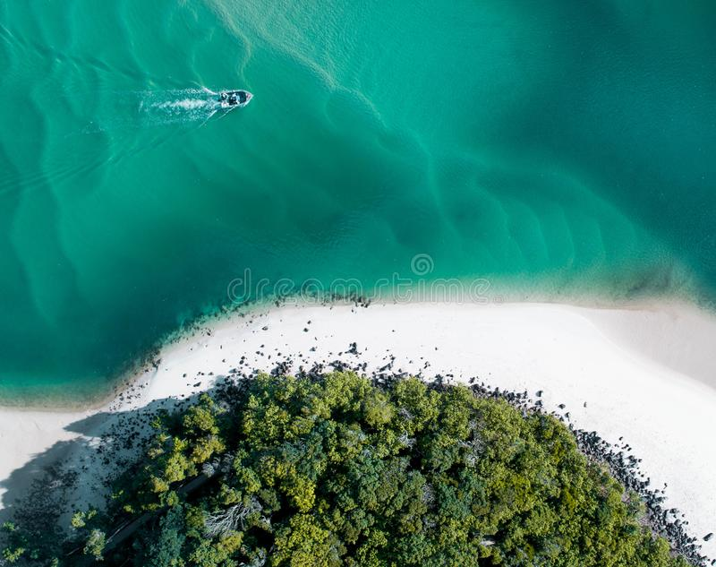 Beach aerial summer with boat and blue tropical water. Beautiful gold coast hot drone shot with boat and sand drift. stock images