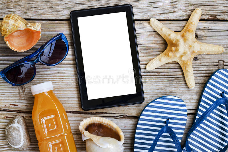 Beach background. Beach accessories, sea souvenirs and a tablet computer on a wooden background. Concept: beach vacation royalty free stock photos