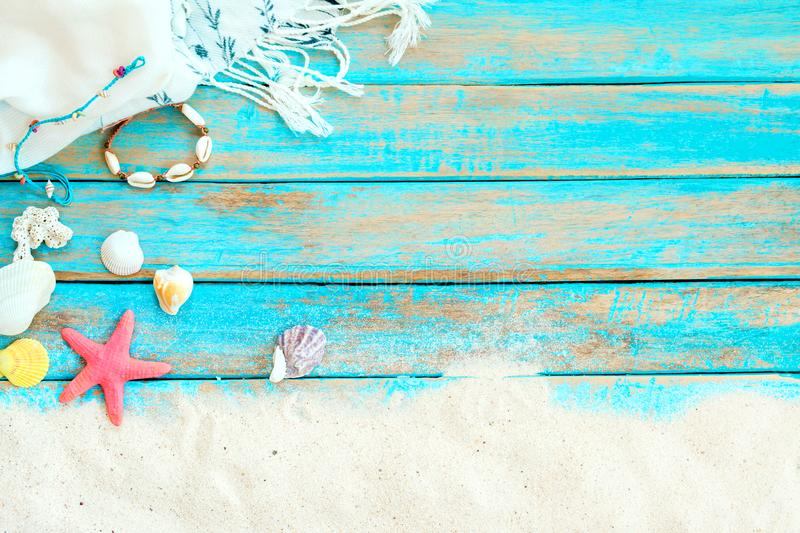 Top viwe of beach sand with white shawl, bracelet made of seashells, starfish, shells and coral on blue wooden background. stock photo