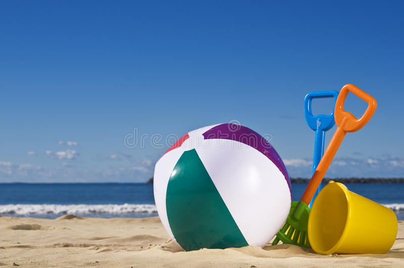 Beach ball. Day at the beach with a beach ball, spade and bucket in the foreground royalty free stock photo