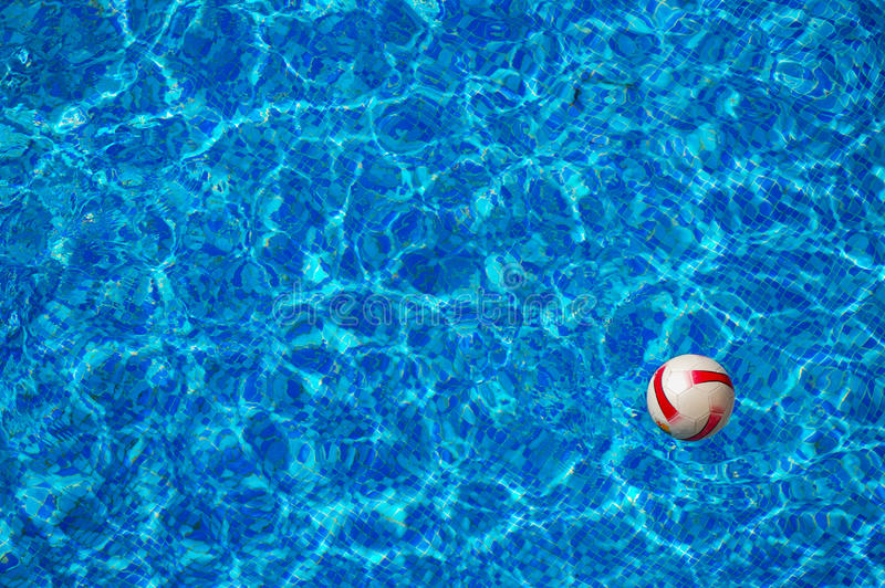 Beach ball floating in swimming pool royalty free stock images