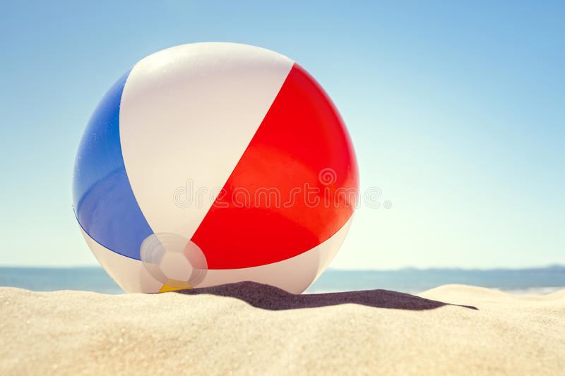 Beach ball on the sand. Beach ball resting in sand dune concept for childhood summer vacations, family holiday and healthy lifestyle stock photography