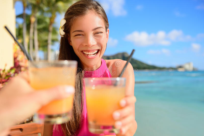 Beach bar party drinking friends toasting cocktail. Beach bar party drinking friends toasting Hawaiian sunset cocktails having fun. Asian woman looking at camera stock images