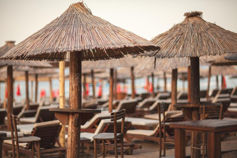 Beach bar with thatched umbrellas and a wooden terrace at an exotic resort. Summer concept royalty free stock image