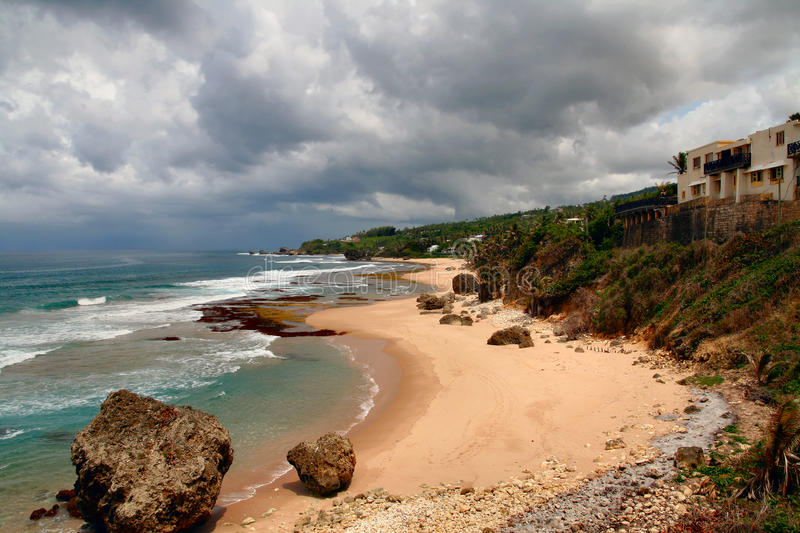 Beach on Barbados. Dark cloudy sky and rocky beach on the East Coast of Barbados on the South Atlantic Ocean, view looking towards town of Bathsheba in the stock images