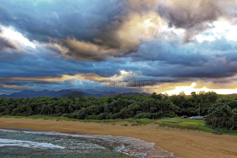 Beach bay with views to hilly country by storm clouds. Clear views over a beach bay towards the hilly countryside of Coffs Harbour, Australia, by a dramatically stock image