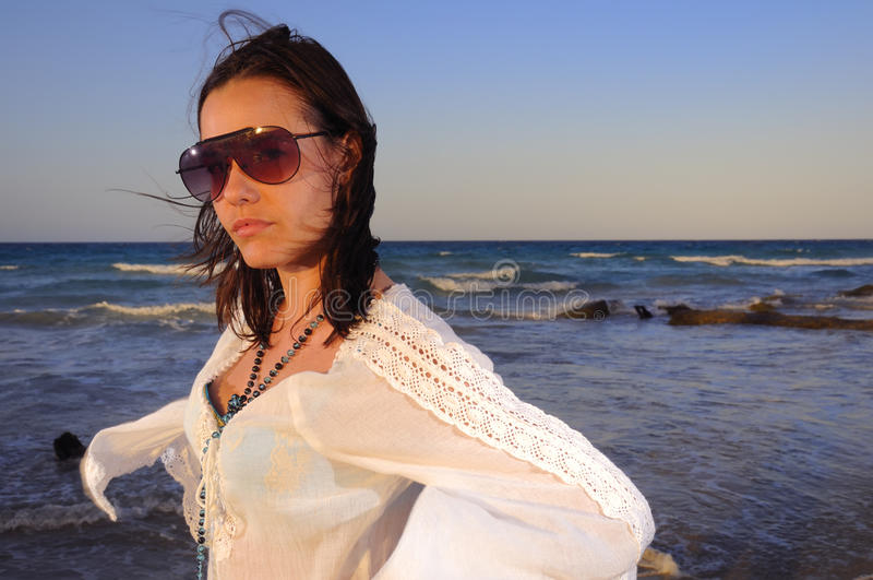 Beach beauty. Portrait of young fashion woman with sunglasses on the beach royalty free stock image