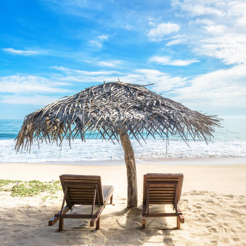 Beach beds with umbrella on tropical beach, Sri Lanka. Sunny view of beautiful sandy shore and ocean royalty free stock photography