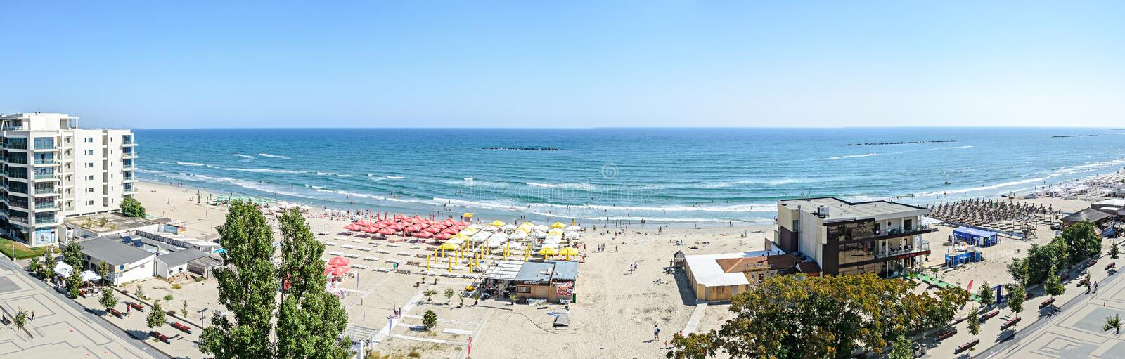 Beach of Black Sea with golden sands, sun umbrellas, sunbeds, blue clear water, bars and hotels. stock photos