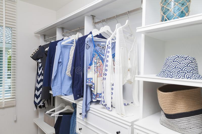 Beach blue clothes hanging in white wardrobe in home. Beach blue clothes and windsurf suit hanging in white wardrobe in home stock photo
