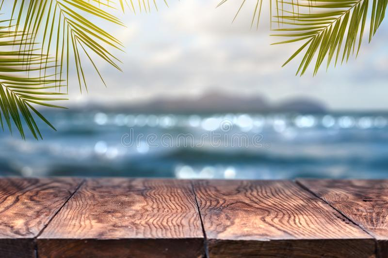 Beach blurred background with palm leaves background with vintage old wood table royalty free stock photography