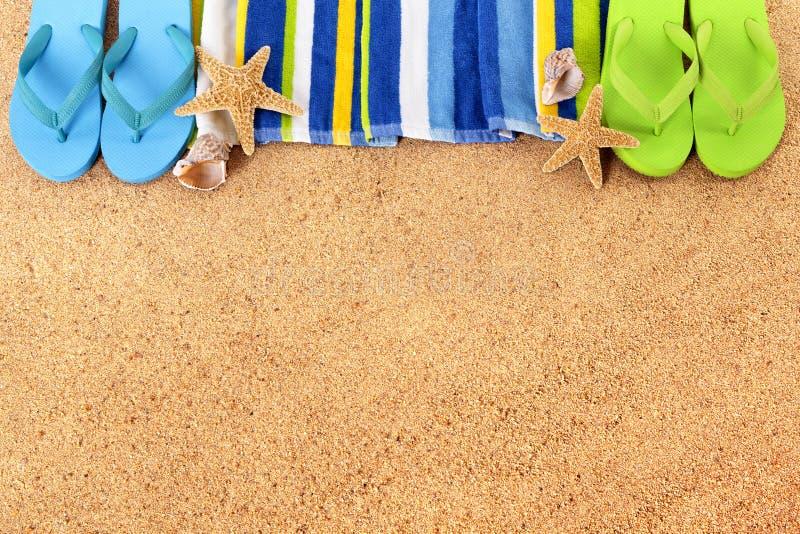 Beach border, flip flops, sand background, copy space. Beach background border with flip flops, towel, starfish and seashells. Copy space stock photo
