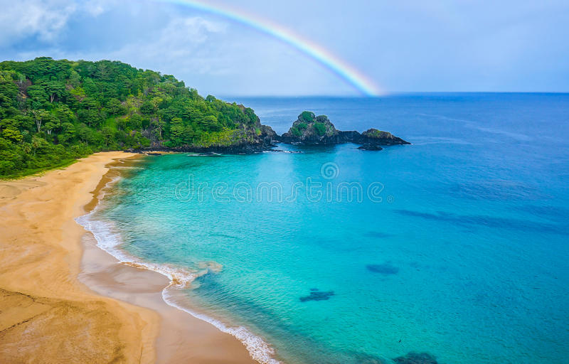 Beach in Brazil with a rainbow on the background. Beach in Fernando de Noronha-Brazil with rainbow on the background and a colorful sea stock images