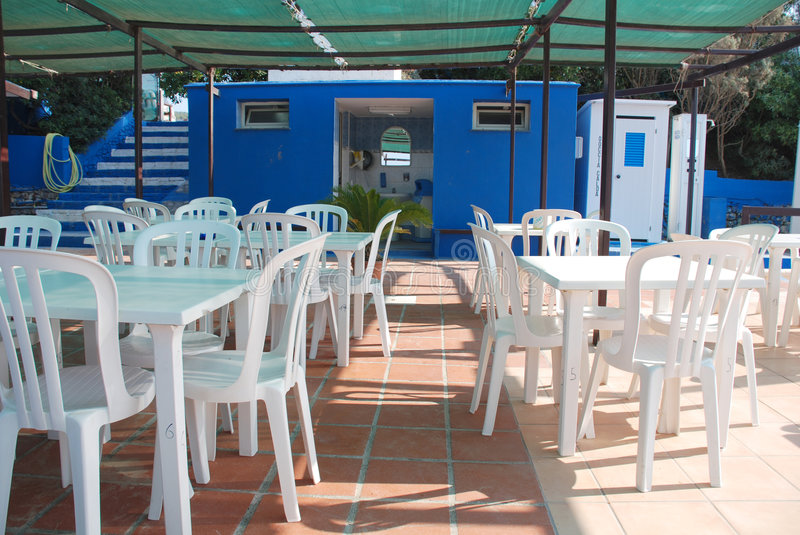 Beach Cafe With Background Bathroom. An empty beach front cafe, deserted out of season. In the background are the cafes beach showers – the white ones on the royalty free stock images