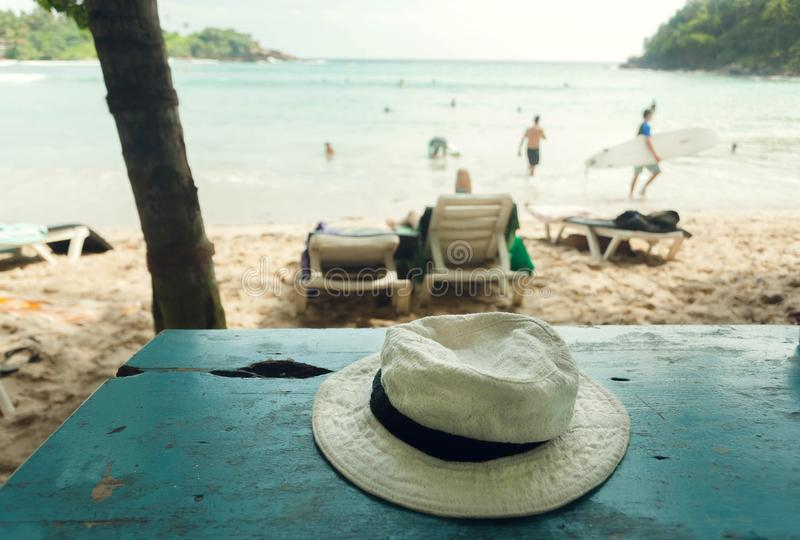 Beach cafe table with hat of a tourist. Tropical landscape with surfers and swimmers. Concept of relaxing vacation. Under sun royalty free stock image