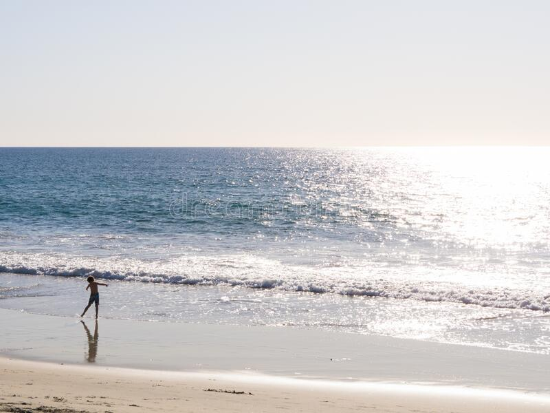 Beach in Carlsbad, California, United States of America. Near San Diego. A kid dancing on a beautiful beach with sunshine. Silver wave. Sea shore stock images