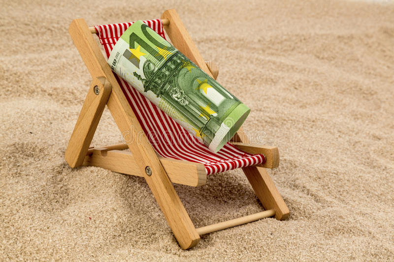 Beach chair with euro banknote. A deck chair with a euro banknote. symbolic photo for saving on holiday and when traveling royalty free stock images