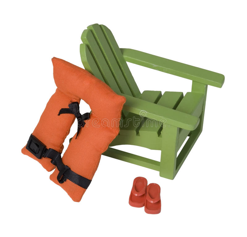 Beach chair with Life Vest and Sandals. Folding beach chair with stripes for relaxing while on vacation royalty free stock image