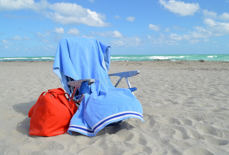 Beach chair, towel and bag by ocean royalty free stock photos
