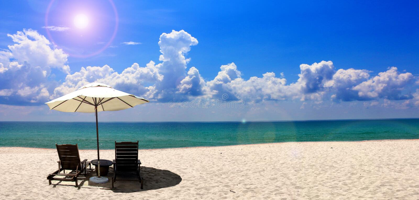 Beach chair and umbrella near the beach. With blue sky stock images