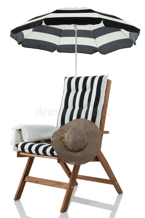 Beach chair with umbrella, towel and sunhat. On white royalty free stock photography