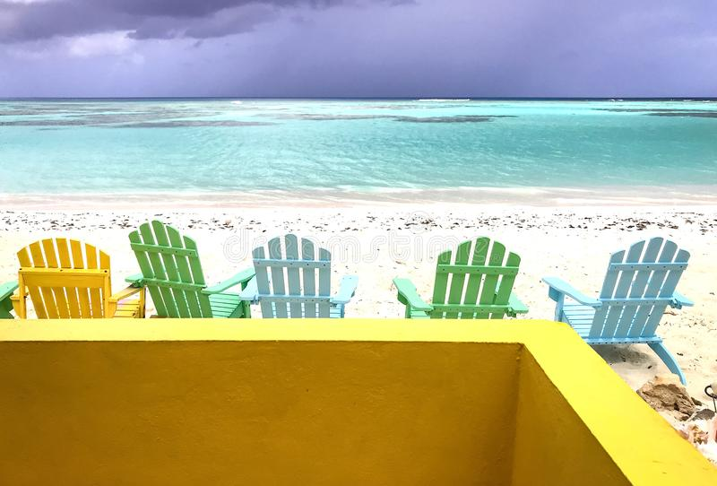 Beach chair and yellow wall, after a rain with a cloudy sky and sunny rays royalty free stock photos