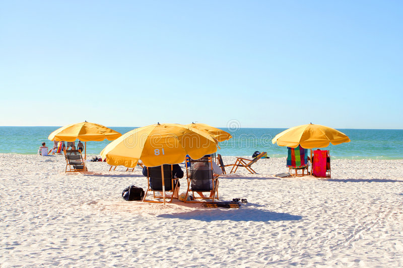 Beach chairs. People relaxing on beach chairs under umbrellas in Clearwater Beach, Florida, USA royalty free stock photography