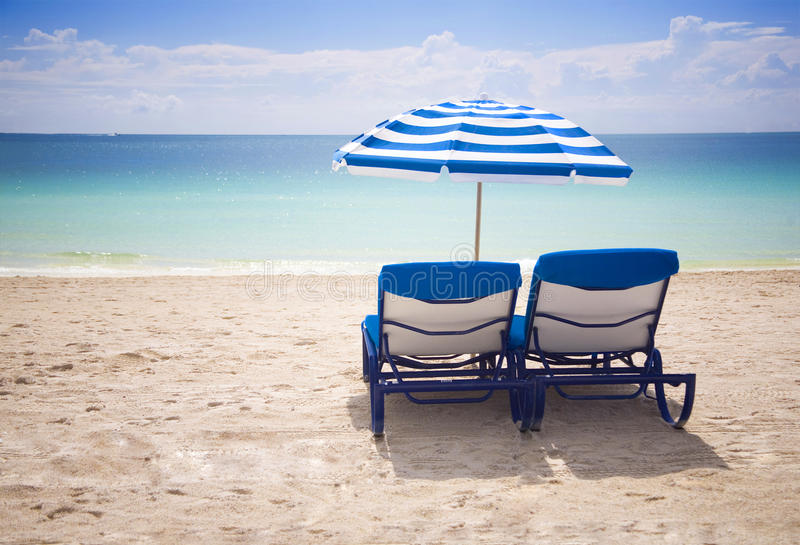 Beach chairs. Blue beach chairs by the ocean stock images