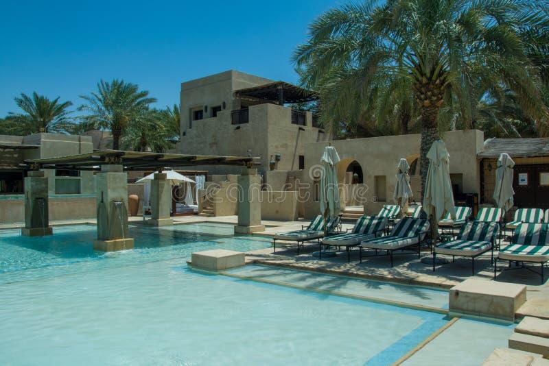 Beach chairs area near swimming pool at luxury arabic desert resort royalty free stock photography