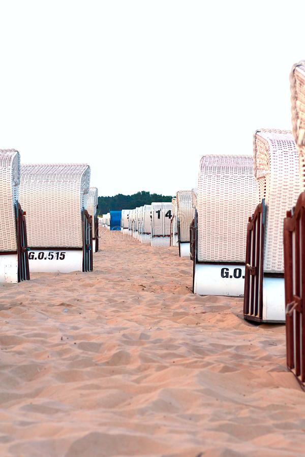 Beach chairs at the Baltic Sea, many white and one blue, vertical royalty free stock images