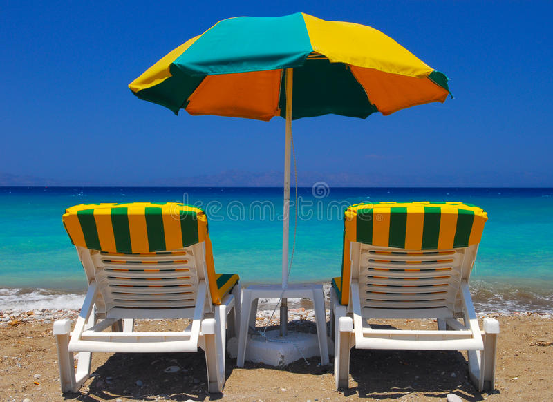 Beach chairs on Rhodes and lie. Fine contradictions of the parasol and chairs on the Greek Beach royalty free stock image