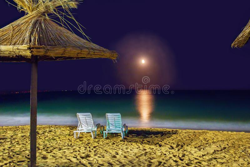 2  beach  chairs on sand  near water.  Sea.  Night on the beach. Warm summer   nights  for  love stock photos